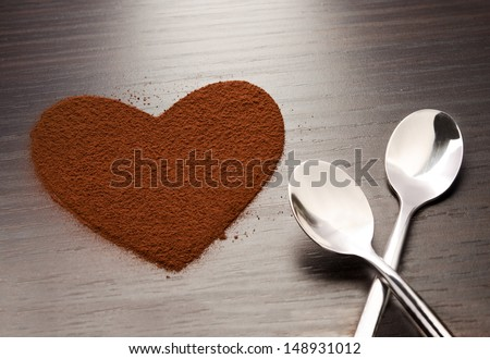 Two spoons beside a heart made from cocoa powder - stock photo