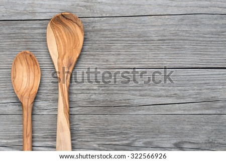 two spoons of olive wood on grey table - stock photo