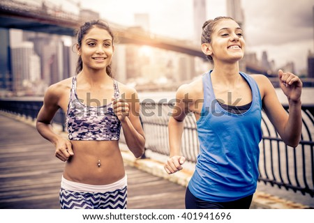 Two sportive pretty women running outdoors at sunset - Female friends training in the morning - stock photo