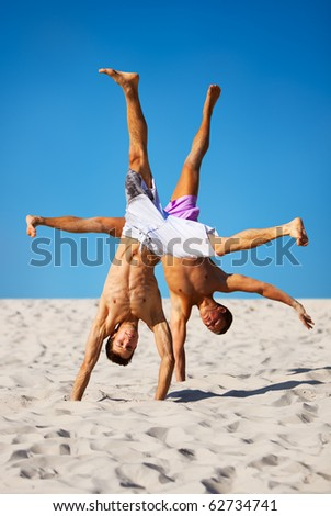 Two sportsmans on beach. On blue sky background. - stock photo