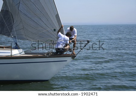Two sportsmen - seamen put a sail on a wind. The yacht will go faster and the victory will be! - stock photo
