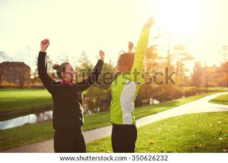 Two sportswomen jumping in park. Running is finished - stock photo