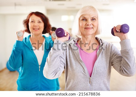 Two sporty females doing exercising with barbells in sport gym  - stock photo