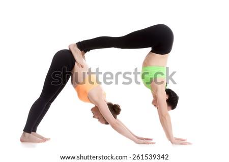Two sporty girl on white background doing acroyoga, yoga with partner, downward-facing dog yoga pose, adho mukha svanasana - stock photo