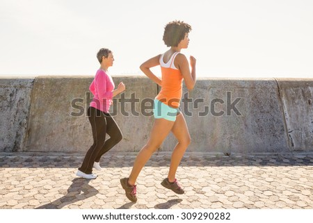 Two sporty women jogging together at promenade - stock photo