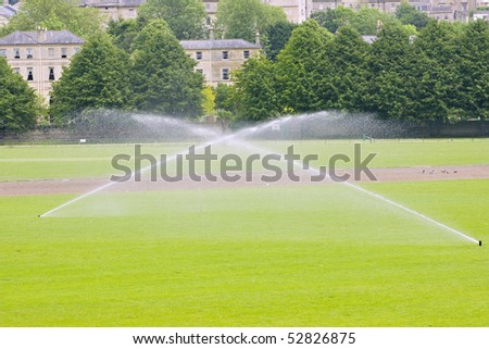 Two sprinklers irrigating a sports field in summer - stock photo