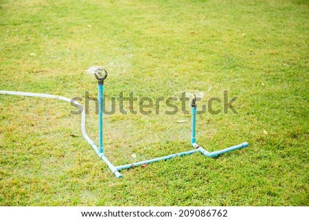 Two sprinklers on green yard - stock photo