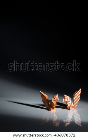 Two squirrels origami made of orange paper isolated on black background.