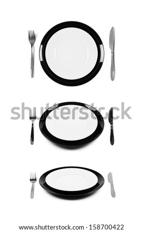 Two stacked white and black plates with fork and knife. Isolated on white. Three angles of view.