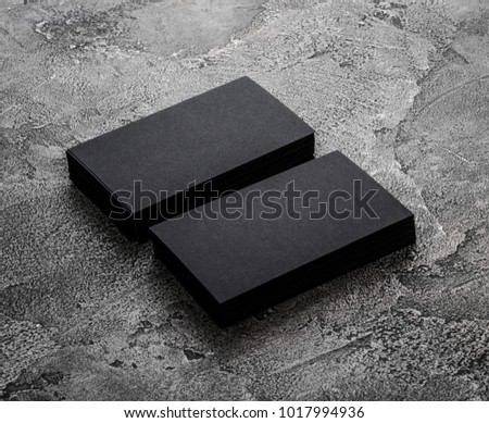 Two stacks of black blank business cards on wooden background.
