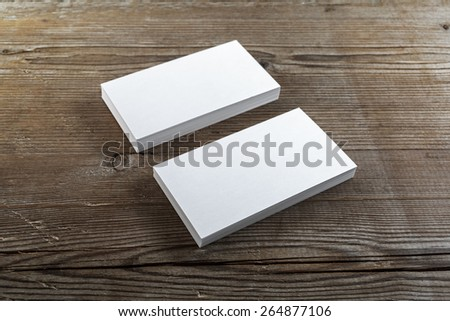 Two stacks of blank business cards on a dark wooden background. Template for branding identity. Shallow depth of field. - stock photo