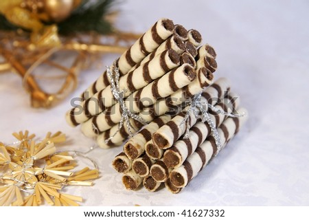 Two stacks of chocolate logs for Christmas and New Year gift, arranged with festive decoration - stock photo
