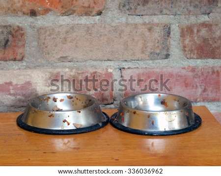 Two stainless  steel dirty dishes for cats food close up on brick wall background.       - stock photo
