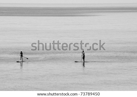 Two stand up paddleboarders on ocean