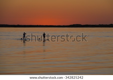 Two Stand up paddlers as silhouettes in the sunset