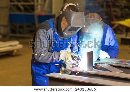 Two steel construction workers welding metal pieces - stock photo