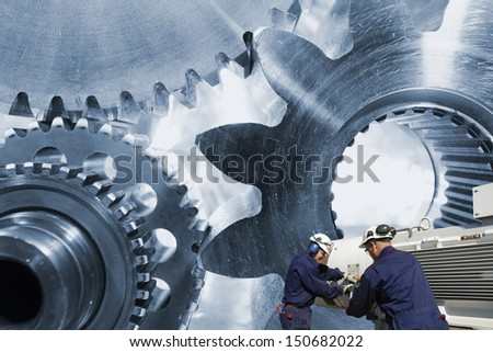 two steel machinery workers involved with large gears and cogwheels - stock photo