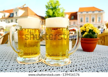 Two steins beer garden in the city, soft focus - stock photo