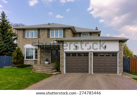 Two-storey house with a lawn and driveway - stock photo