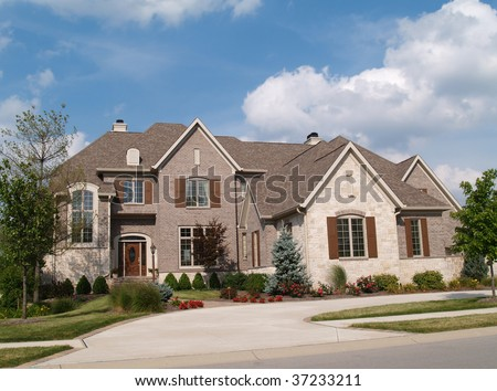 Two story brick and stone residential home with circle driveway. - stock photo
