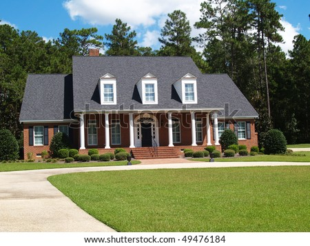 Two story brick residential home with large front porch and side entrance garage. - stock photo