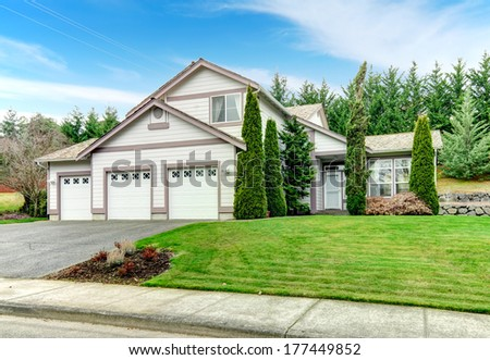 Two story clapboard siding house with garage, drive way, green lawn and fir trees