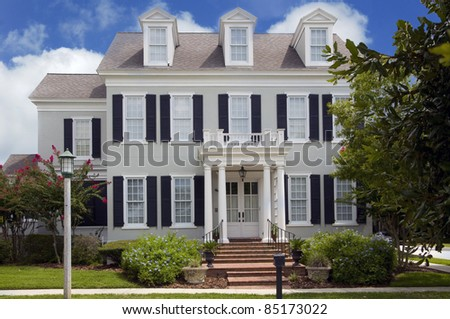 Two story colonial style home with shutters - stock photo