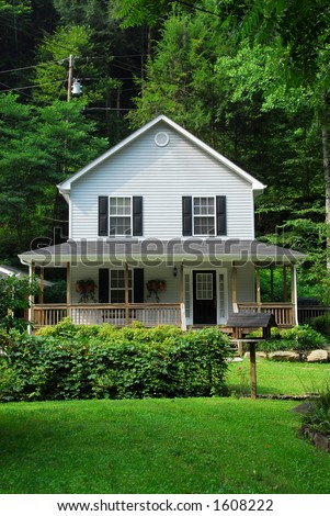 Two-story country farm house in a forest setting. - stock photo