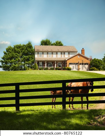 Two story home with a mare and a pony standing along the fence in front of the house in the front yard in Kentucky, USA. - stock photo