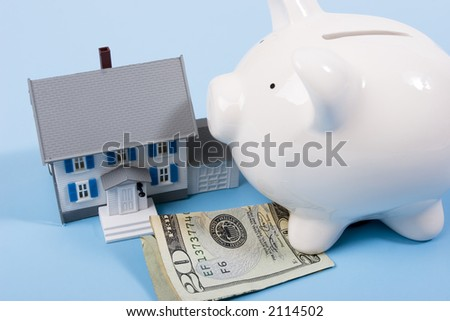 Two-story house with twenty dollar bill and a piggy bank - stock photo