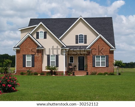 Two story residential home with both brick and board siding on the facade. - stock photo