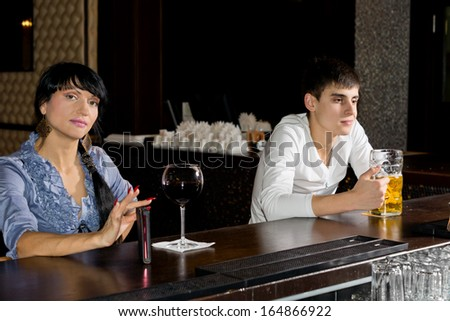 Two strangers drinking at a bar with a pretty stylish woman and attractive young man ignoring each other as they drink alone - stock photo