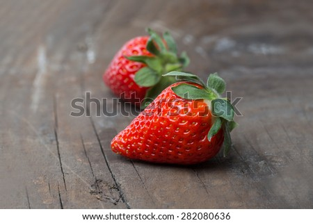 Two Strawberries on a rustic wooden background - stock photo