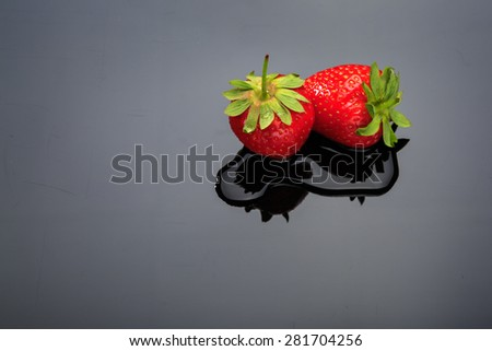 Two strawberries on dark background. with copy space.
