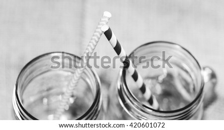 Two straws crossing up close in separate jars used as glasses. In black and white.
