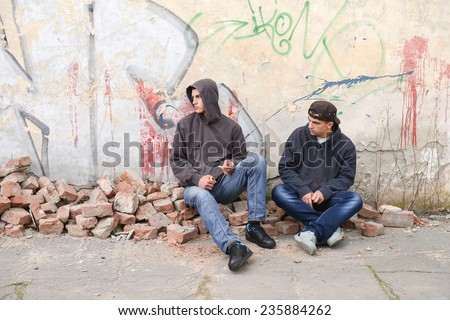 Two street hooligans or rappers sitting against a graffiti painted wall with a ball near them - stock photo