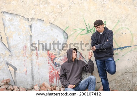 two street hooligans or rappers standing against a graffiti painted wall and sharing a cigarette - stock photo