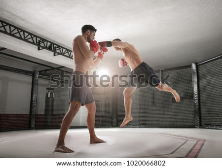 Two strong kickboxers fighting in gym