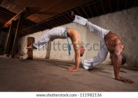 Two strong male capoeira experts fighting indoors - stock photo