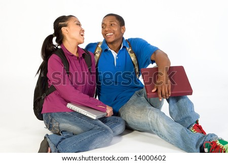 Two Students are sitting on the ground looking at each other. Both wear backpacks and he carries a notebook. Horizontally framed photograph - stock photo