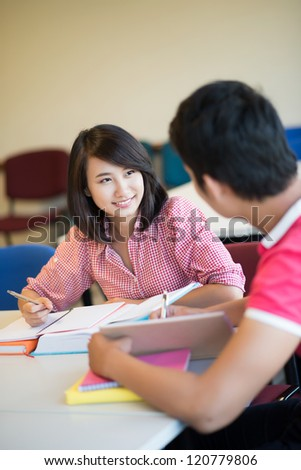 Two students communicating while doing classwork - stock photo