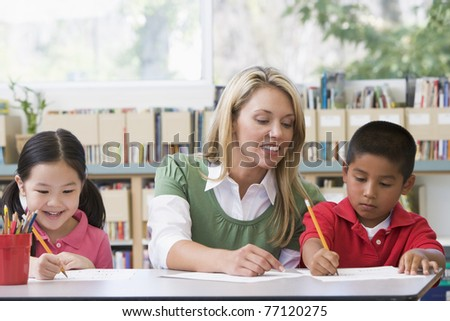 Two students in class writing with teacher helping