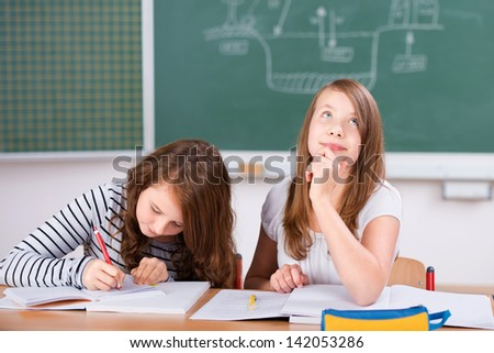 Two students in classroom studying their lesson in school - stock photo