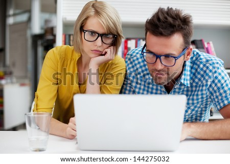 Two students learning in library on computer - stock photo