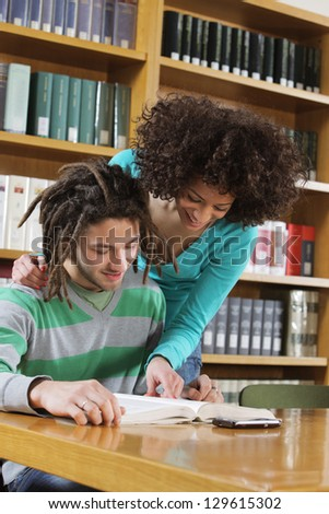Two students learning together indoors in library