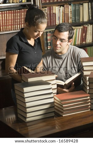 Two students looking at books in an office. Vertically framed photo. - stock photo