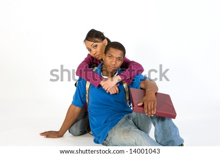 Two students looking at the camera while she has her arms around his neck. Horizontally framed photograph - stock photo
