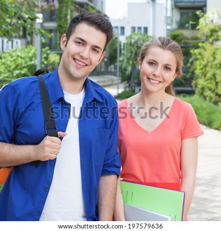 Two students on campus laughing at camera - stock photo