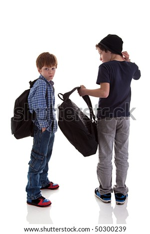 two students seen with his back to the school bags, one looking back, isolated on white background - stock photo