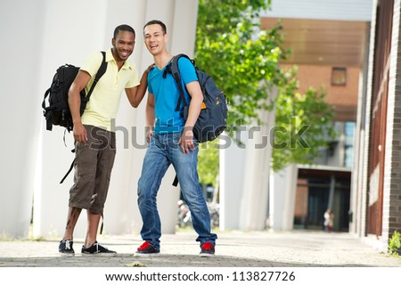 Two students smiling outdoors. Full length portrait of African American and Caucasian students laughing and looking at camera. - stock photo